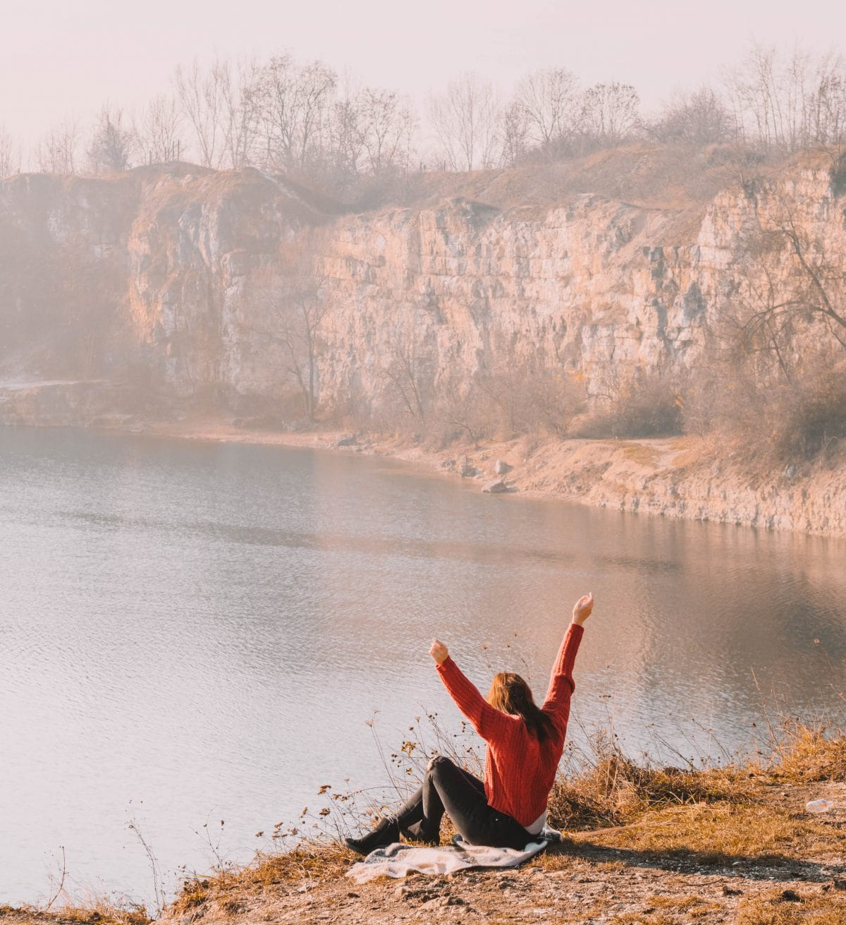 Der Blick erstreckt sich über von der Klippe über den See bis zu endenen Steinwand, während die Sonne aufgeht streckt sich eine Frau ihr entegegen.