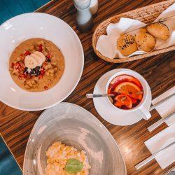 Porridge garniert mit Granatapfel und Bananenscheiben, samt einen mit Orange garnierten Früchtetee